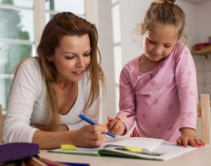 A mum helping her daughter with homework