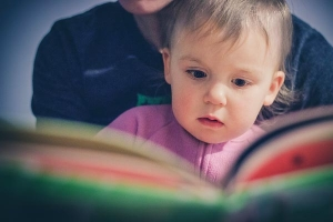 Toddler reading with a parent