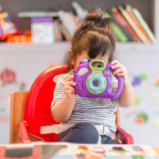 Toddler with play camera at nursery school