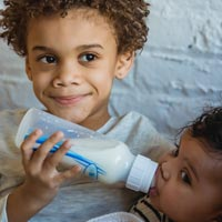 A young boy feeds bottled formula milk to his sibling